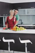 Stock Photo of young couple have fun in modern kitchen