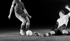Football players in competition for the ball Stock Photos