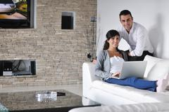 Joyful couple relax and work on laptop computer at modern home Stock Photos