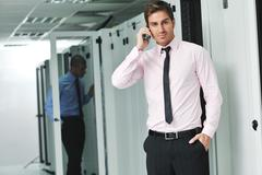 Stock Photo of it engeneer talking by phone at network room