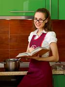 Young woman preparing in the kitchen with cook book Stock Photos