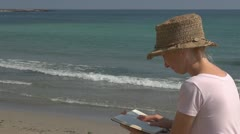 Beautiful woman reading on the beach, sea, ocean, romantic, meditative, learning Stock Footage