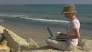 Businesswoman working on laptop on the beach, busy, ocean, lifestyle, wireless Stock Footage