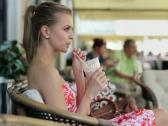 Happy attractive young woman drinking cocktail in cafe NTSC Stock Footage
