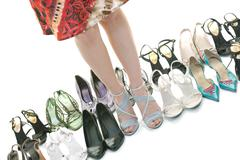 Stock Photo of pretty young woman with buying shoes addiction, isolated on white background