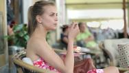 Attractive young woman eating tasty dessert in cafe  HD Stock Footage