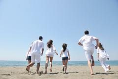 happy people group have fun and running on beach - stock photo