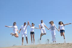 Stock Photo of happy people group have fun and running on beach