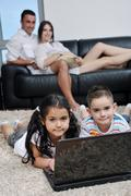 happy young family have fun and working on laptop at home - stock photo