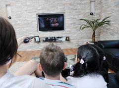 family wathching flat tv at modern home indoor - stock photo