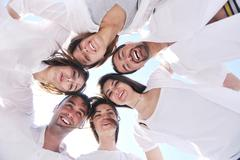 Stock Photo of group of happy young people in circle at beach