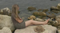 Blonde woman relaxing on the beach, young, rock, ocean, meditation,  coastline Stock Footage