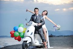 Just married couple on the beach ride white scooter Stock Photos