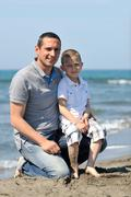 Stock Photo of happy father and son have fun and enjoy time on beach