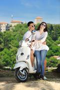 portrait of happy young love couple on scooter enjoying summer time - stock photo