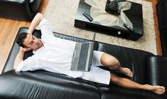 portrait of a relaxed young guy using laptop at home - stock photo