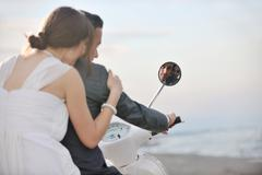 just married couple on the beach ride white scooter - stock photo
