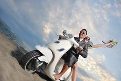 Stock Photo of just married couple on the beach ride white scooter