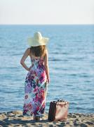 woman with suitcase on the beach - stock photo