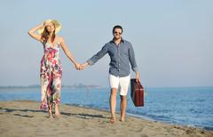 Stock Photo of couple on beach with travel bag