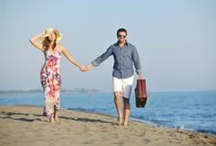 couple on beach with travel bag - stock photo