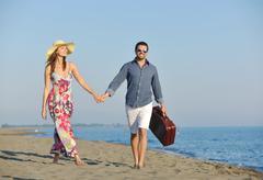Couple on beach with travel bag Stock Photos