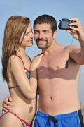 happy young couple in love taking photos on beach - stock photo