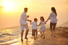 Happy young family have fun on beach at sunset Stock Photos