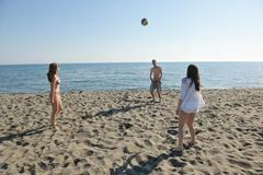 Stock Photo of young people group have fun and play beach volleyball
