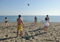 Young people group have fun and play beach volleyball Stock Photos