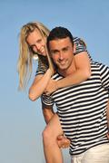 happy young couple have romantic time on beach - stock photo