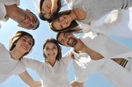 Group of happy young people in circle at beach Stock Photos