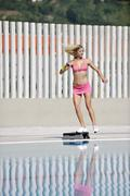 woman fitness exercise at poolside - stock photo