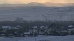 Winter time over the village sunset snow blizzard twilight mountain hill houses Stock Footage