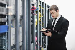 Stock Photo of it businessman withnotebook in network server room
