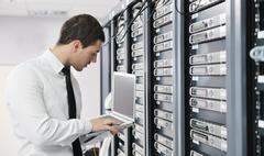 Businessman with laptop in network server room Stock Photos