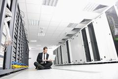 businessman with laptop in network server room - stock photo