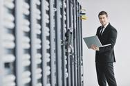Stock Photo of businessman with laptop in network server room
