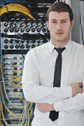young engeneer in datacenter server room - stock photo