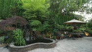 Stock Video Footage of Paver Stone Garden Backyard Waterfall with Furniture and Umbrella 1080p