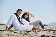 young couple enjoying  picnic on the beach - stock photo