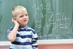 happy young boy at first grade math classes - stock photo
