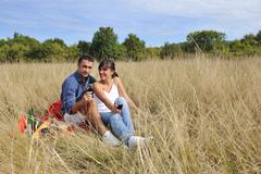 Stock Photo of happy couple enjoying countryside picnic in long grass