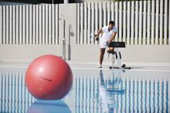 Stock Photo of young healthy athlete man exercise at poolside