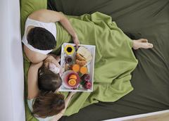 Stock Photo of happy young family eat breakfast in bed