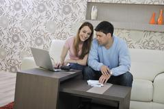 young couple working on laptop at home - stock photo