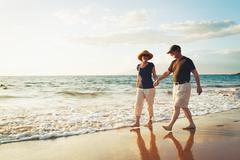 Senior couple enjoying sunset at the beach Stock Photos