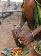 Indian woman slices chilis on the sharp blade of a sickle Stock Photos
