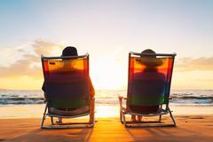 Happy romantic couple enjoying beautiful sunset at the beach Stock Photos