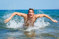 Man swimming butterfly strokes in ocean Stock Photos